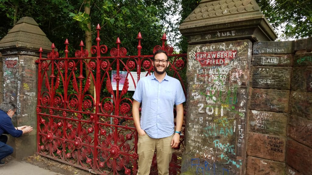 The author standing in front of Strawberry Fields gate in Liverpool, UK.