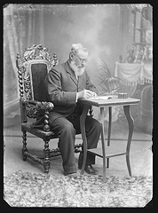 Seated portrait of a man with a beard writing a document.